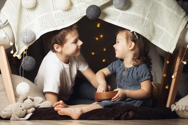 Irmãos em uma cabana de cadeiras e cobertores. irmão e irmã brincando em casa