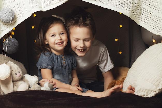 Irmãos em uma cabana de cadeiras e cobertores