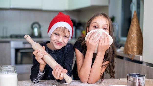 Irmãos estão cozinhando e posando na cozinha, menino com chapéu de natal e rolo de massa, menina com a massa. rostos com farinha. ideia de criança feliz