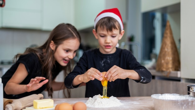 Irmãos estão cozinhando na cozinha, menino com chapéu de natal. ideia de criança feliz