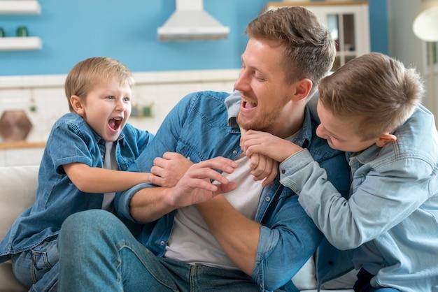 Irmãos fazendo cócegas em seu pai