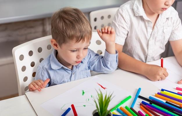Irmãos fazendo desenhos na escola doméstica do jardim de infância Foto Premium