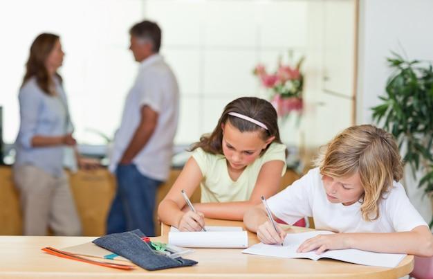 Irmãos fazendo lição de casa com os pais por trás deles