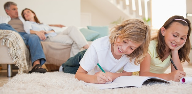 Irmãos fazendo sua lição de casa no tapete com os pais por trás deles
