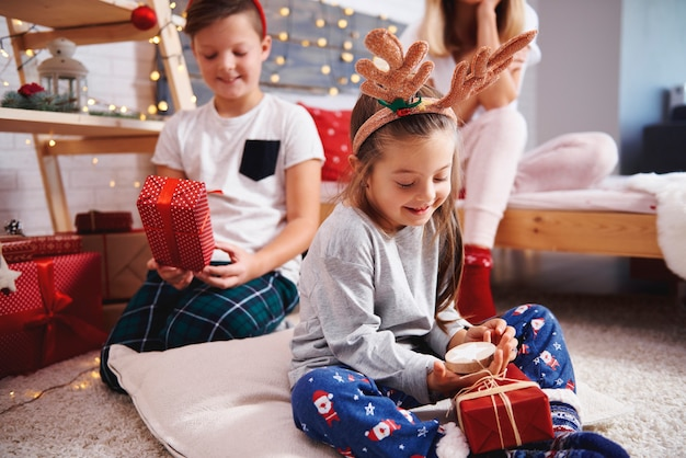 Irmãos felizes abrindo os presentes de natal