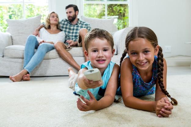 Irmãos felizes assistindo tv contra pais relaxando em casa