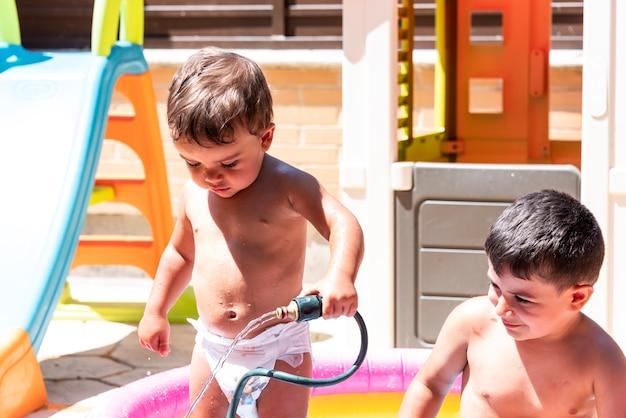 Irmãos felizes brincam com mangueiras de água no quintal.