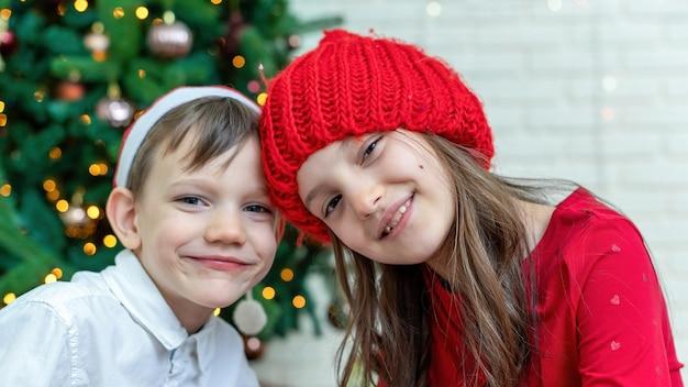 Irmãos felizes com roupas de natal no chão perto da árvore de natal em casa. ideia de família feliz