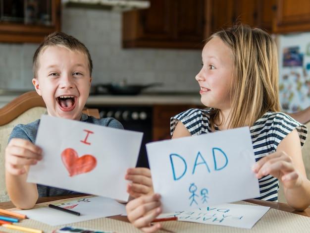 Irmãos felizes desenhando para seu pai
