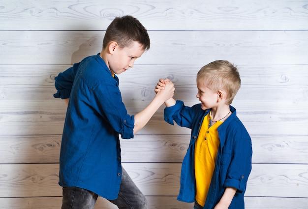 Irmãos felizes e amigáveis durante o jogo de queda de braço. dois amigos positivos lutando pelas mãos