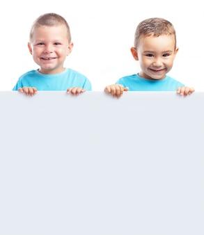 Irmãos felizes que mostram uma tabuleta vazio