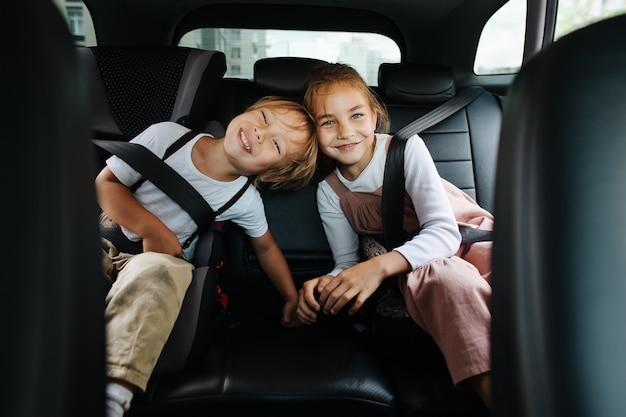 Irmãos felizes, sentados no banco de trás de um carro, posando para uma foto. tocando com as cabeças, olhando para a câmera.