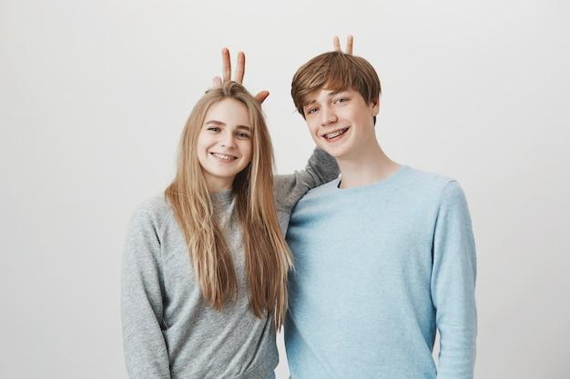 Irmãos felizes sorrindo. menina e menino com aparelho fazem orelhas de coelho atrás