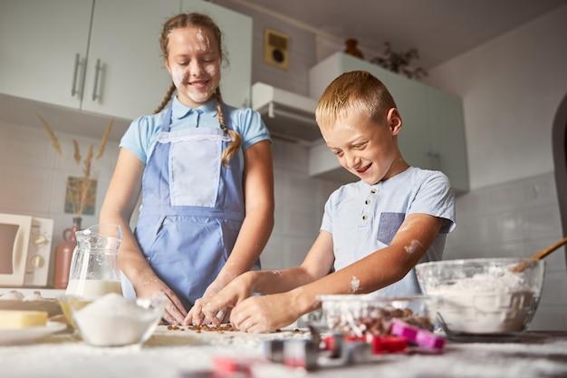 Irmãos fofos trabalhando para fazer massa de biscoito na cozinha