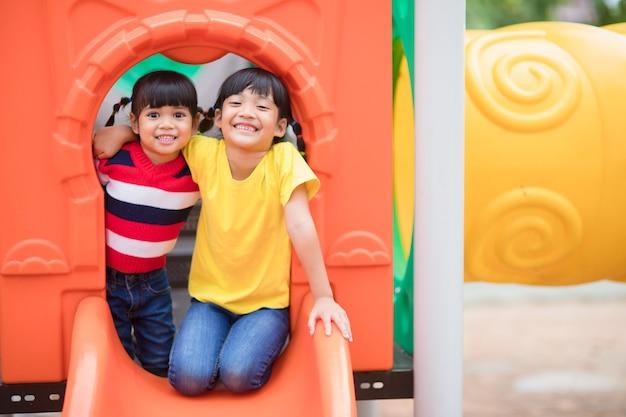 Irmãos garotinhas fofas se divertindo no playground ao ar livre em um dia ensolarado de verão