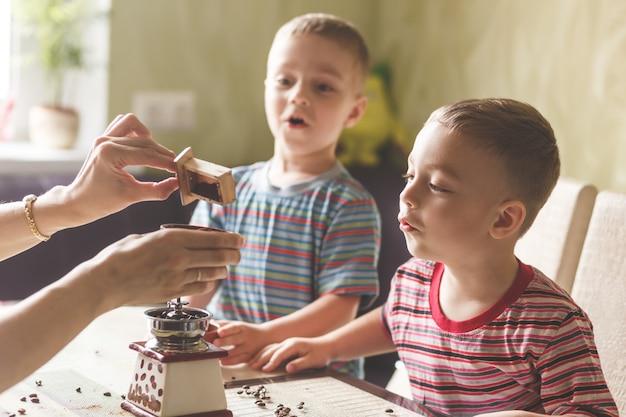 Irmãos gêmeos ajudando a mãe a moer café