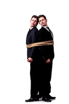 Irmãos gêmeos amarrados com corda isolada no branco