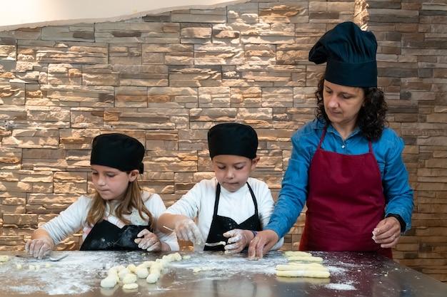 Irmãos gêmeos de menino e menina preparando massa com a mãe em uma oficina de culinária vestidos como chefs