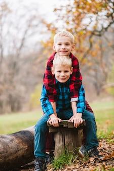 Irmãos gêmeos felizes em camisas quadriculadas sentam-se no banco de madeira no outono passado. conceito de família e amizade com crianças do sexo masculino sorrindo e abraçando