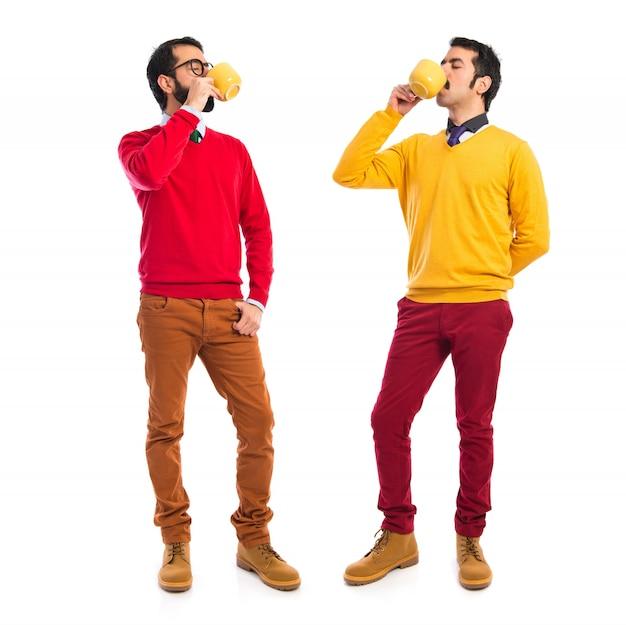 Irmãos gêmeos, segurando xícara de café
