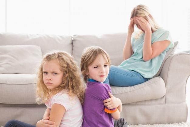 Irmãos irritados sentados braços cruzados com mãe triste no sofá