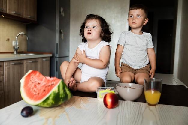Irmãos jovens bonitos na cozinha