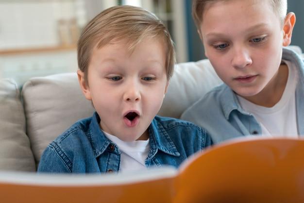 Irmãos, lendo um livro juntos vista frontal