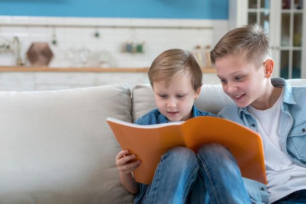 Irmãos lendo um livro juntos