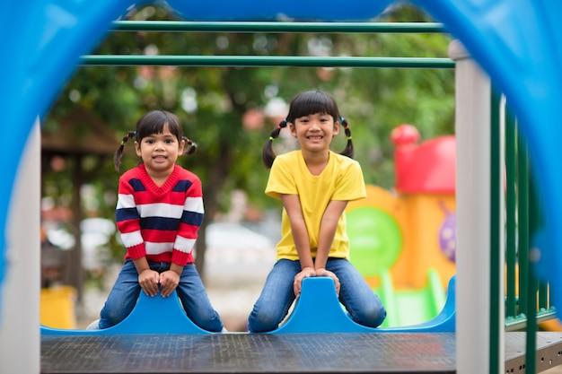 Irmãos lindos de meninas se divertindo no parquinho ao ar livre em um dia ensolarado de verão