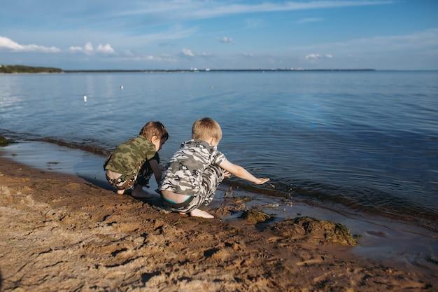 Irmãos meninos brincando com areia e algas no mar lindo céu no fundo
