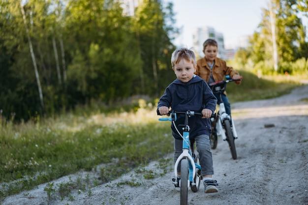 Irmãos meninos estão pedalando juntos no campo no verão