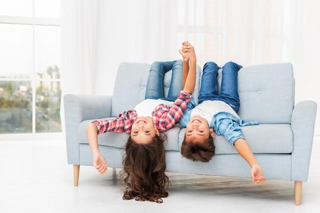 Irmãos na borda do sofá com a cabeça pendurada