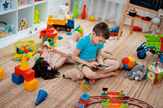 Irmãos no chão brincando com smartphones