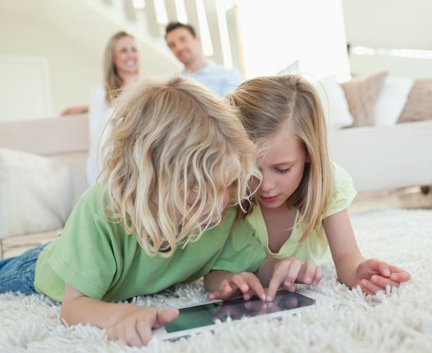Irmãos no chão com um tablet e pais atrás deles