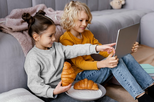 Irmãos no sofá com tablet