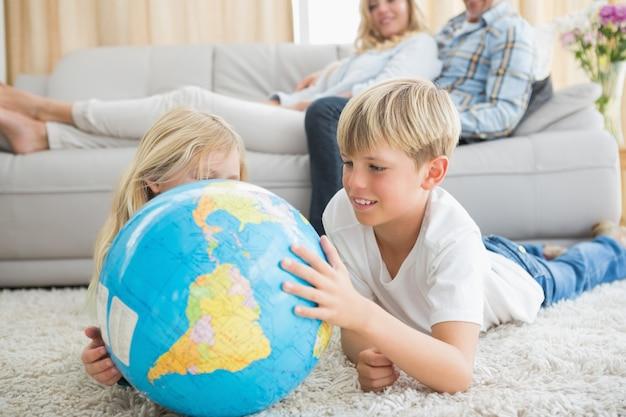 Irmãos olhando o globo no chão