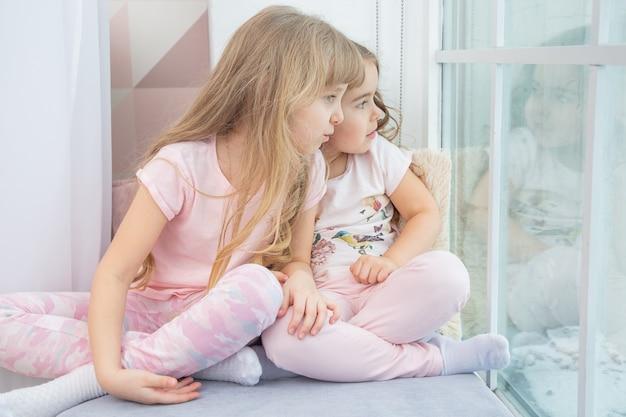 Irmãos pequenos bonitos sentados no peitoril da janela em casa olha pela janela para a neve, retrato de lindas meninas no peitoril da sala no inverno. adorável criança pensativa na criança rosa, bonita durante a contemplação.