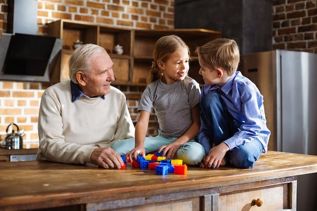 Irmãos pequenos e alegres brincando com blocos de construção enquanto o avô está por perto
