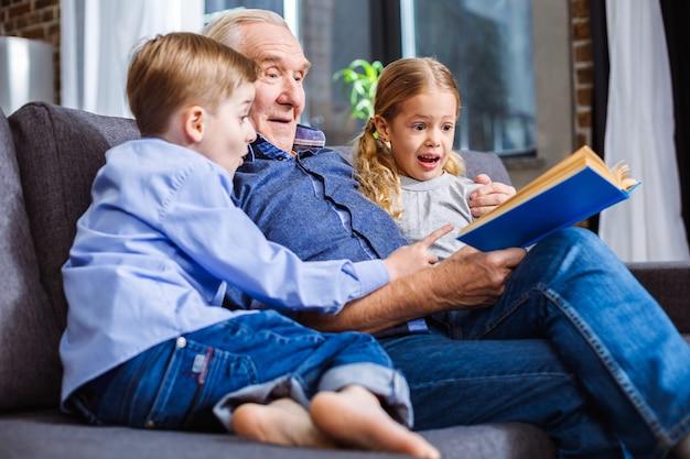 Irmãos pequenos e alegres lendo um livro enquanto descansam com o avô no sofá