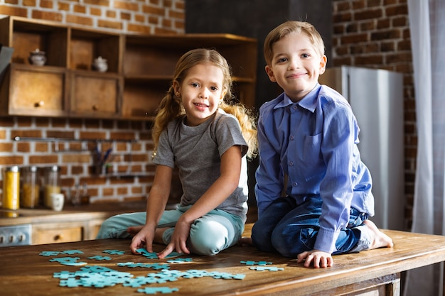 Irmãos pequenos e alegres sentados na cozinha montando quebra-cabeças
