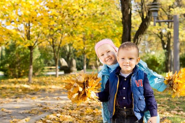 Irmãos pequenos e sorridentes felizes brincando com as folhas de outono em um parque com folhagem colorida de outono