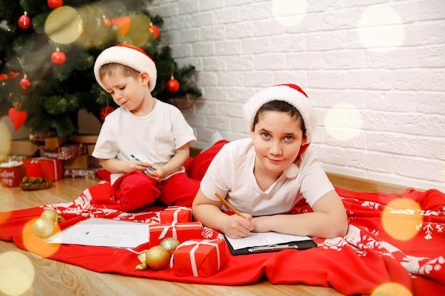 Irmãos pequenos fofos escrevendo uma carta para o papai noel com chapéu vermelho