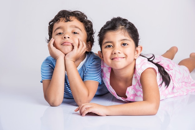 Irmãos pequenos indianos se abraçando, retrato de 2 crianças indianas, menino indiano e menina sentados juntos sobre um fundo branco, menino indiano alegre e menina posando para uma foto