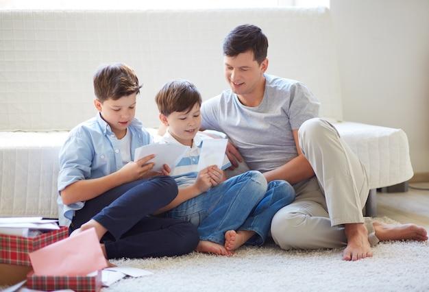 Irmãos prestam atenção a fotos com seu pai