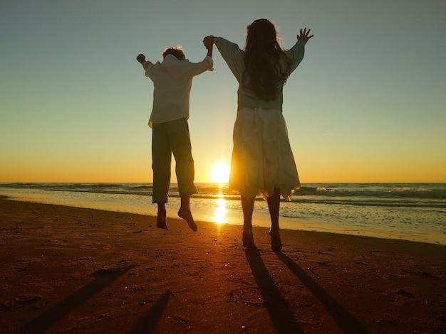 Irmãos pulando na praia cercada pelo mar durante o pôr do sol