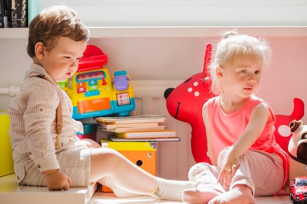 Irmãos sentados com brinquedos posando