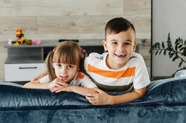 Irmãos sentados juntos no sofá