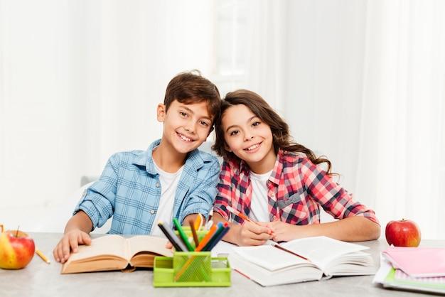 Irmãos sorridentes fazendo dever de casa juntos