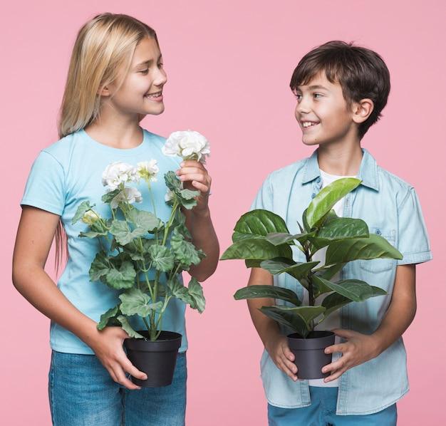 Irmãos sorridentes segurando o vaso de flores