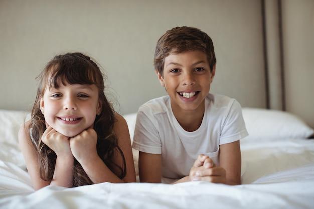 Irmãos sorrindo na cama